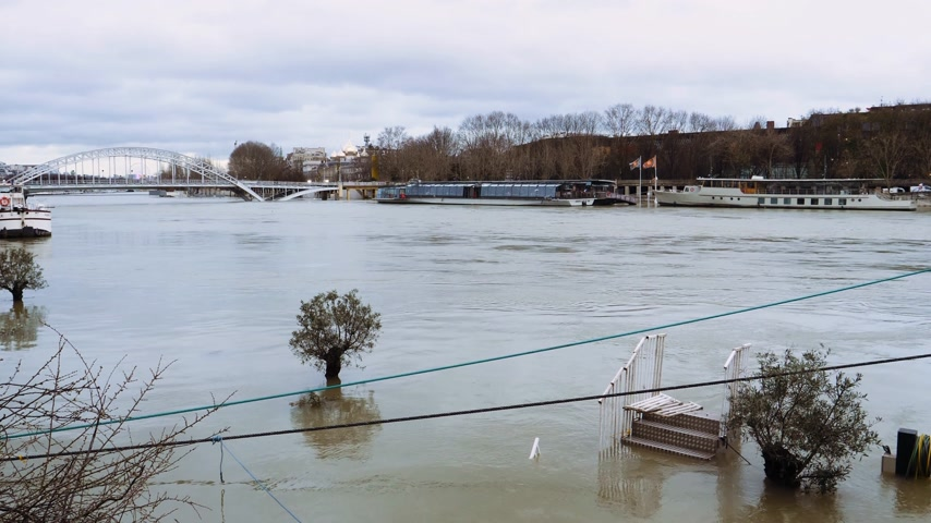 boathouse : Cinematic colors over overflow flooding embankments on the Seine river in Paris after heavy rains with Eiffel Tower in the background - news footage aerial still drone black and white Stock Footage