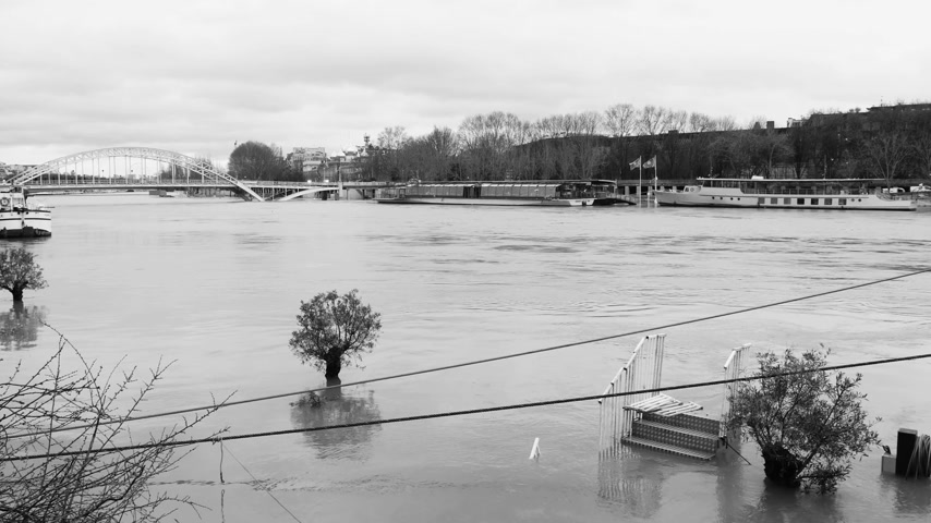 boathouse : Overflow flooding embankments on the Seine river in Paris after heavy rains with Eiffel Tower in the background - news footage aerial still drone black and white