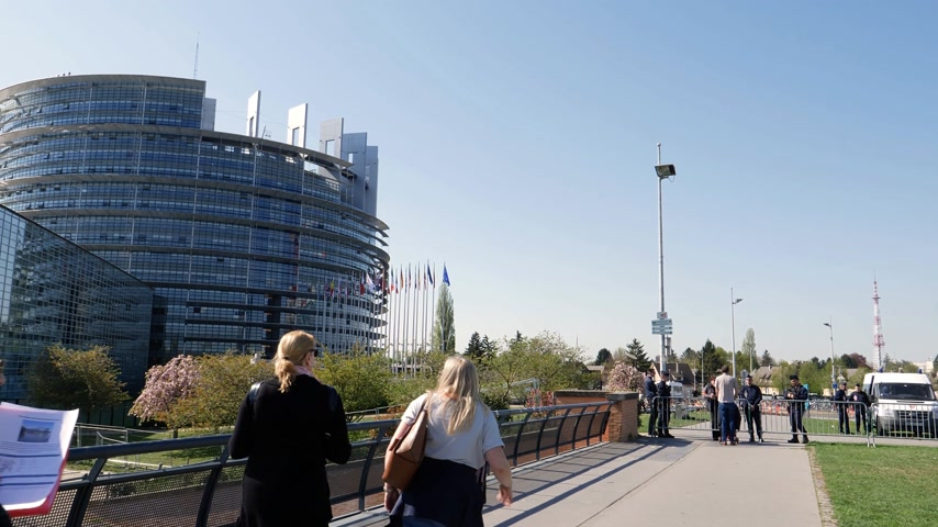 bancário : STRASBOURG, FRANCE - CIRCA 2018: Group of women walking toward police officers surveilling over a steel fence the European Parliament building in 4k UHD format