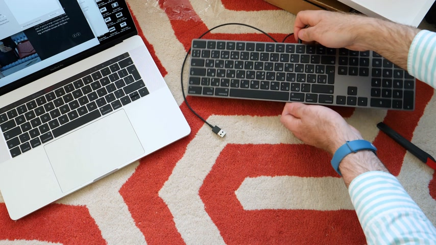 apple computers : LONDON, UNITED KINGDOM - APR 15, 2018: Man unboxing installing charging pairing Bluetooth to Apple MacBook pro laptop 15 inch to new Magic Keyboard with Numeric Keypad Space Gray Cyrillic Russian keyboard
