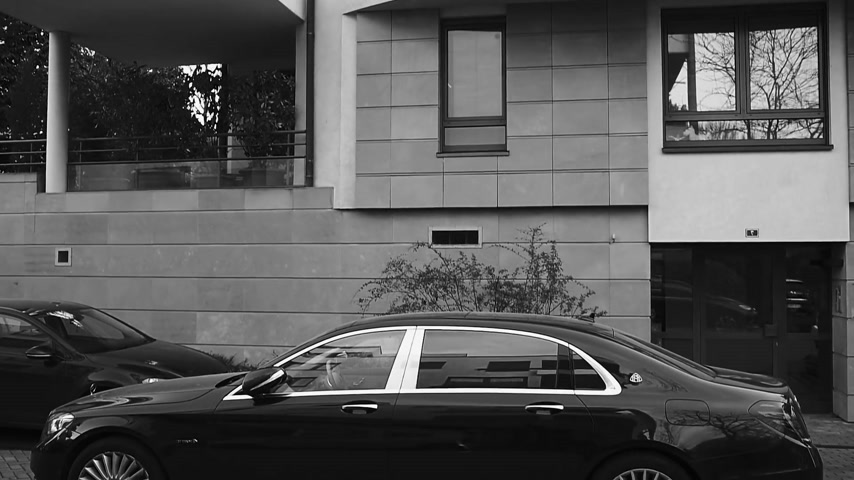 limuzína : PARIS, FRANCE - APR 8, 2018: Side view of new luxury blue Mercedes-Maybach s600 4matic awd limousine parked on a Parisian street near residential building with family on bicycle riding - black and white-