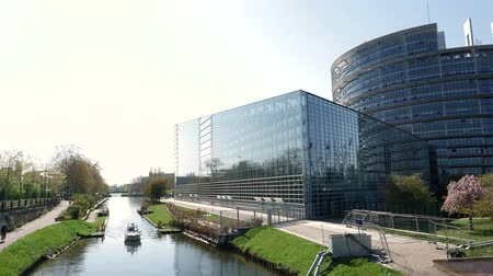 alargamento : Front facade of the European Parliament building in 4k UHD format with National Gendarmerie boat surveilling Ill river canal - view from above