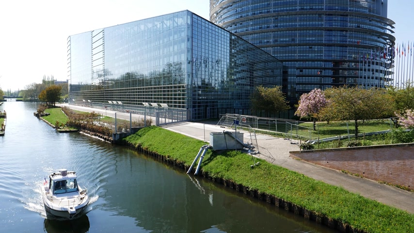 alargamento : Front facade of the European Parliament building in 4k UHD format with National Gendarmerie boat surveilling Ill river canal view from above with flare sunlight Stock Footage