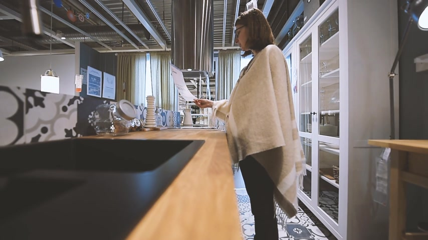 consumerism : PARIS, FRANCE - CIRCA 2018: Modern IKEA furniture store woman customer browsing through diverse furniture, decoration warehouse goods - checking price for new kitchen set Stock Footage