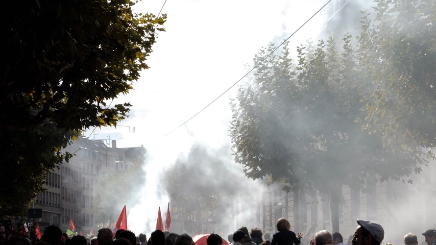 gritante : STRASBOURG, FRANCE - SEP 12, 2018: Smoke grenade thrown by people during French Nationwide day of protest against labor reform proposed by Emmanuel Macron Government