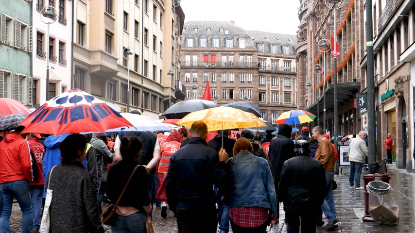 nationwide : STRASBOURG, FRANCE - SEP 12, 2018: Rear view of people with umbrella marching at French Nationwide day of protest against labor reform proposed by Emmanuel Macron Government
