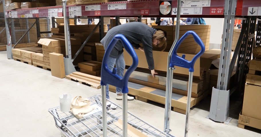 stockpile : PARIS, FRANCE - CIRCA 2018: Woman selecting cardboard box from the shelves inside the warehouse of IKEA store putting on the shopping cart - time lapse fast motion