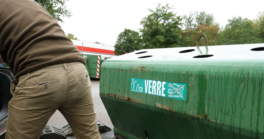 reprocessing : PARIS, FRANCE - CIRCA 2018: Man taking from car trunk glass waste bottles for recycling at facility with different glass packaging bottle waste. waste management dechetterie in France