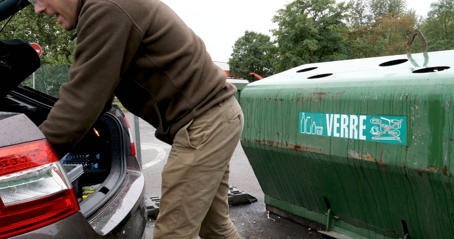 recusar : PARIS, FRANCE - CIRCA 2018: Man taking from car trunk glass waste bottles for recycling at facility with different glass packaging bottle waste. waste management dechetterie in France for home waste Stock Footage