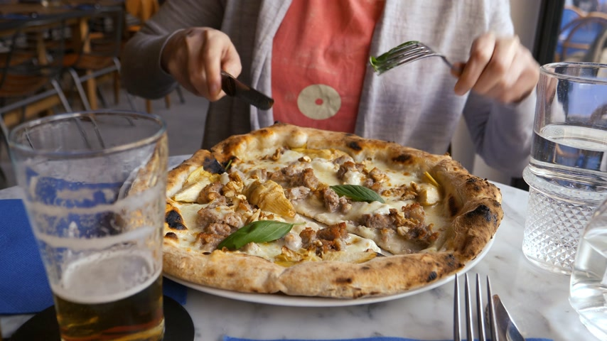 olasz konyha : Woman eating cutting delicious pizza Salsiccia e Carciofi made from Artichoke heart, Campania buffalo mozzarella, black pork sausage, pecan-