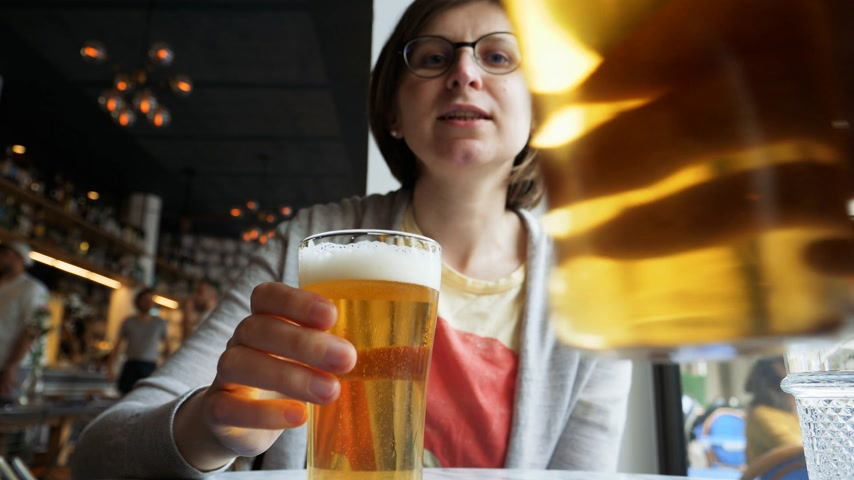 Октоберфест : Woman drinking beer in luxury restaurant pub - toast with male hand during a date or city evening Стоковые видеозаписи