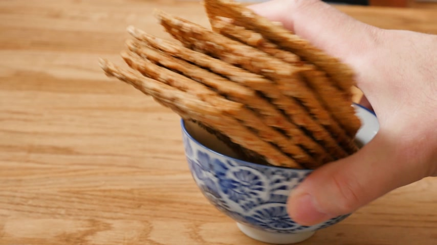 de baixa caloria : Man hand taking from Japanese bowl with healthy brown rye bread crisps on a wooden cutting board