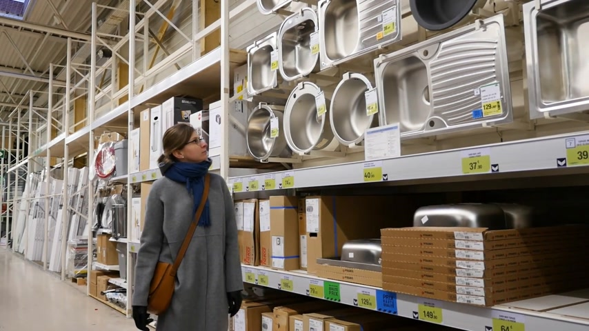 encanador : MARSEILLE, FRANCE - CIRCA 2017: French woman shopping buying for new sanitary furniture for the bathroom and kitchen - choosing between ceramic, stainless steel sink for her new home