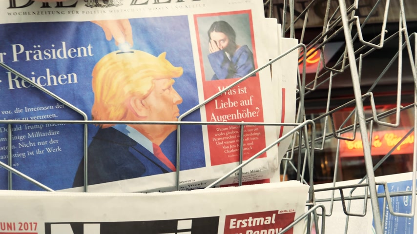 newspaper cover : PARIS, FRANCE - JUN 12, 2017: man buying Die Zeit at press kiosk German newspaper with Donald Trump and Nazi message on the Bild magazine-
