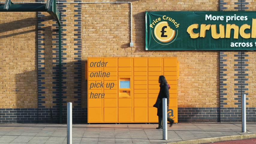 пакет : CAMDEN, LONDON - UNITED KINGDOM - CIRCA 2018: Black ethnicity woman and Caucasian man walking in front of the Amazon Locker at the Morrisons supermarket