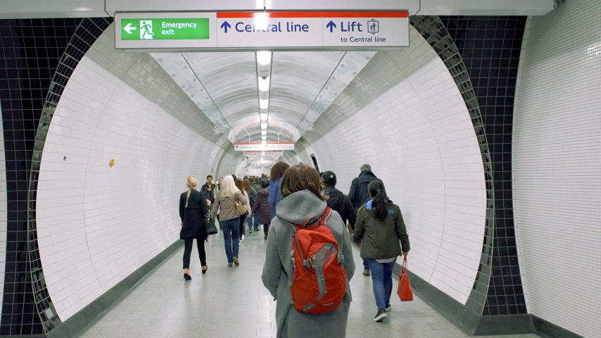odchodu : London, United Kingdom - Circa 2018: London underground metro tube with commuters walking to get the train to Central Line with security signs to Emergency Exit and lift - travel in British capital newsworthy footage in 4k
