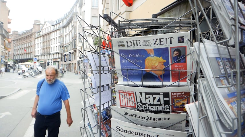 newspaper cover : PARIS, FRANCE - JUN 12, 2017: City slow motion man in front of Die Zeit at press kiosk German newspaper with Donald Trump and Nazi message on the Bild magazine-