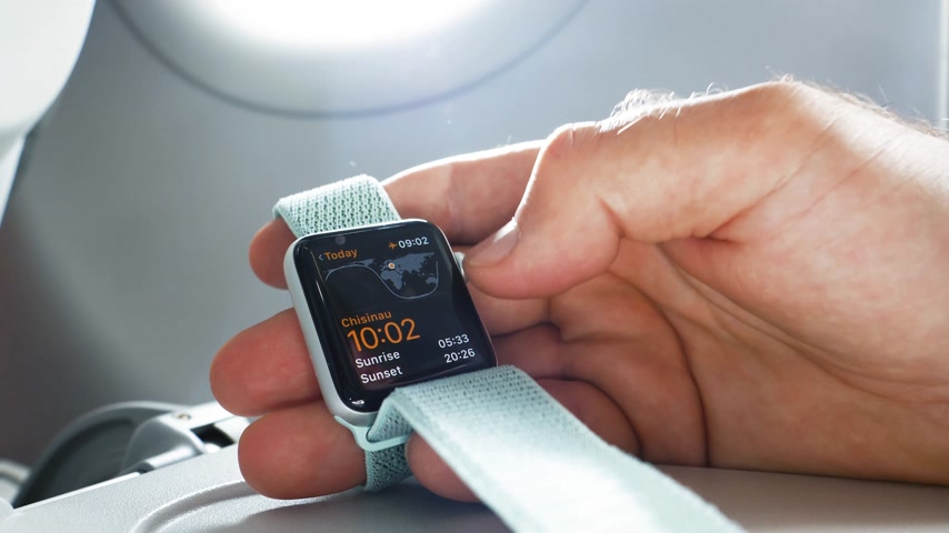 wristband : USA - CIRCA 2018: Man hand using Apple Watch made by Apple computers in the business class near the window of a modern airplane aircraft wising time world clock app