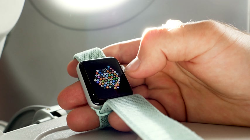 wristband : USA - CIRCA 2018: Man hand using Apple Watch made by Apple computers in the business class near the window of a modern plane. Selecting the new app Stock Footage