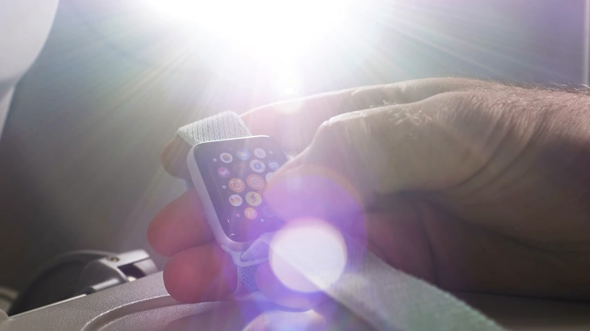 wristband : USA - CIRCA 2018: Sunlight flare over man hand using Apple Watch made by Apple computers in the business class near the window of a modern plane. Choosing Apple music and no music synchronized with phone Stock Footage
