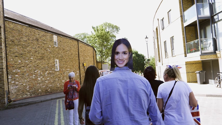 windsor : WINDSOR, BERKSHIRE, UNITED KINGDOM - MAY 19, 2018: Man wearing with Meghan Marke mask walking on Windsor street to attend the royal wedding marriage celebration of Prince Harry and Meghan Markle Stock Footage