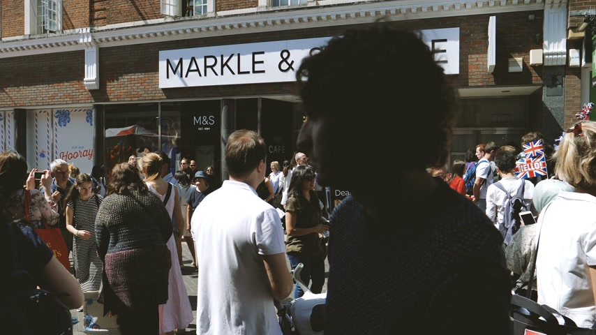 windsor : Windsor, United Kingdom - May 19, 2018: Crowd of people in front of Marks and Spencer store is seen with its name changed to Markle and Sparkle during Royal wedding ProRes HQ codec
