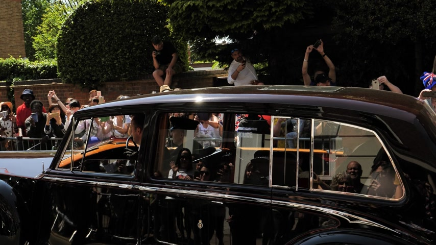 windsor : WINDSOR, UNITED KINGDOM - MAY 19, 2018: Crowd admiring the Rolls Royce in cortege of the newlywed carriage in Windsor Castle procession celebrate wedding of Prince Harry of Wales and Ms. Meghan Markle Stock Footage