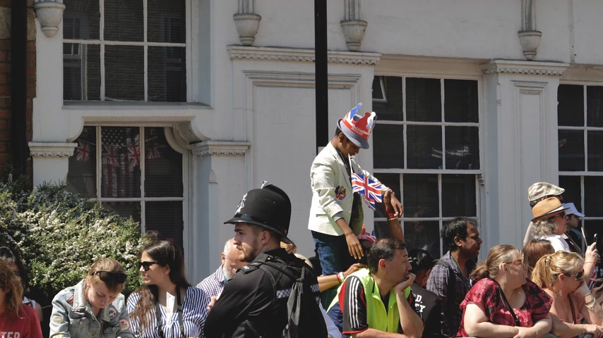 meghan markle : WINDSOR, BERKSHIRE, UNITED KINGDOM - MAY 19, 2018: Black ethnicity boy on shoulders raised enough to see royal wedding marriage celebration of Prince Harry and Meghan Markle - waiving union jack flag