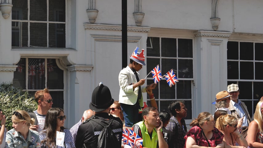 sendika : WINDSOR, BERKSHIRE, UNITED KINGDOM - MAY 19, 2018: Black ethnicity boy on shoulders raised enough to see royal wedding marriage celebration of Prince Harry and Meghan Markle - waiving union jack flag