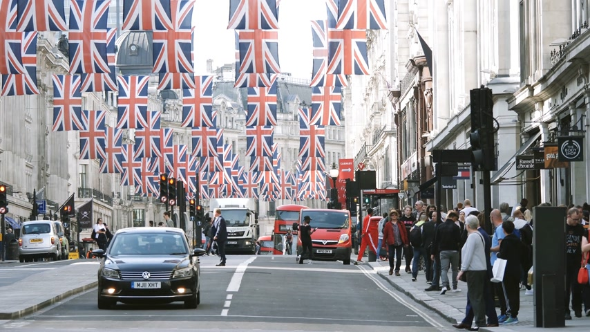 маркировка : LONDON, UNITED KINGDOM - MAY 18, 2018: Pedestrians near bus station and Volkswagen car under Union Jack Flags on Regent Street Royal Wedding between Prince Harry and Meghan Markle cinematic flare