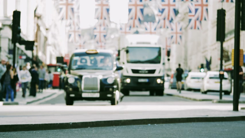 meghan markle : Best defocused view of pedestrians red bus trucks cyclists under Union Jack Flags on Regent Street a day before Royal Wedding between Prince Harry and Meghan Markle