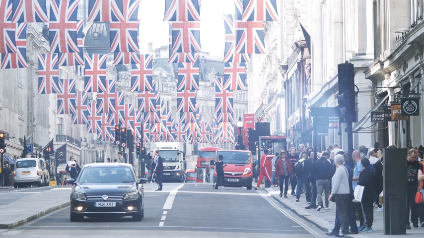 london cab : LONDON, UNITED KINGDOM - MAY 18, 2018: Pedestrians near bus station and Volkswagen car under Union Jack Flags on Regent Street Royal Wedding between Prince Harry and Meghan Markle cinematic flare