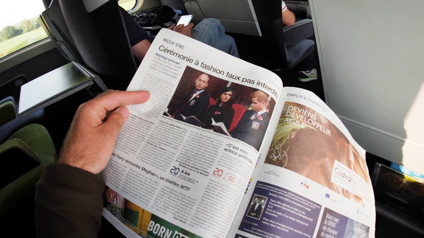 william : FRANCE - MAY 20, 2018: Man reading 20 Minutes front cover newspaper in moving SNCF first class train featuring portraits of Prince William, Prince Harry and Meghan Markle Royal Wedding Stock Footage