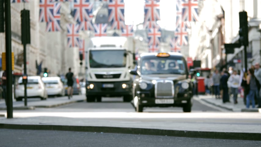 london cab : Cinematic defocused street scene view of pedestrians red bus trucks cyclists under Union Jack Flags on Regent Street a day before Royal Wedding between Prince Harry and Meghan Markle Stock Footage