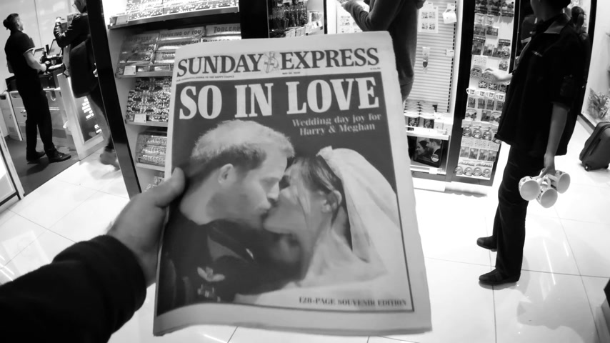 meghan markle : LONDON, UK - MAY 20, 2018: POV The Sunday Express front cover newspaper British press kiosk featuring portraits of Prince Harry and Meghan Markle Royal Wedding So In Love black and white Stock Footage