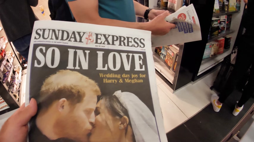 prins : LONDEN, Verenigd Koninkrijk - 20 mei 2018: Crowd reading The Sunday Express voorblad krant Britse perskiosk met portretten van Prins Harry en Meghan Markle Royal Wedding So In Love Stockvideo