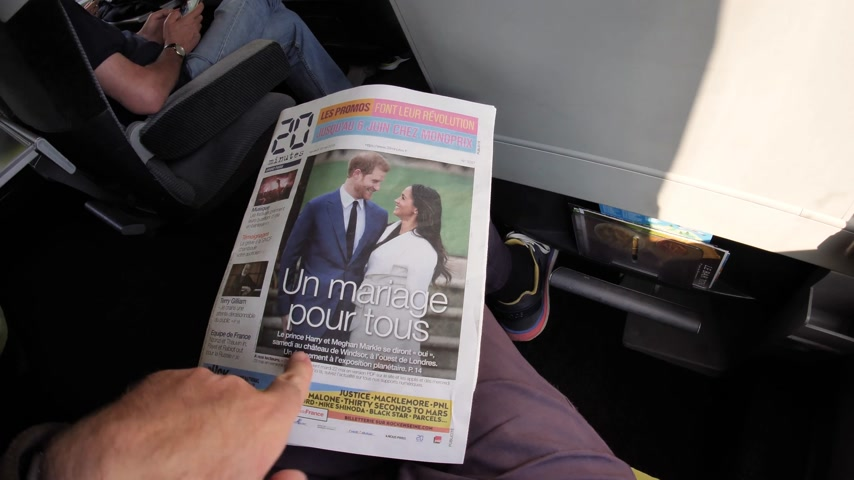 meghan markle : FRANCE - MAY 20, 2018: Man reading 20 Minutes front cover newspaper in moving SNCF first class train featuring portraits of Prince Harry and Meghan Markle Royal Wedding