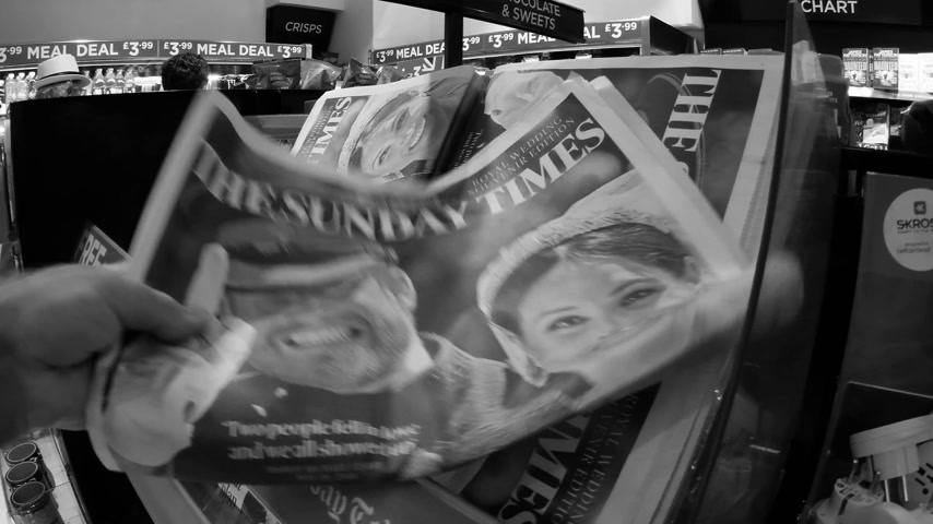 domingo : LONDON, ENGLAND - MAY 20, 2018: POV The Sunday Express front cover newspaper in British press kiosk featuring portraits of Prince Harry and Meghan Markle following the Royal Wedding black and white Stock Footage