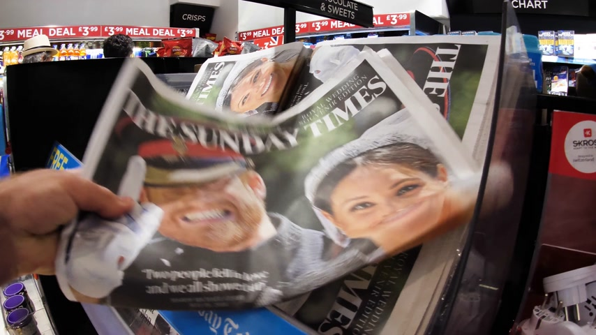 meghan markle : LONDON, ENGLAND - MAY 20, 2018: POV The Sunday Express front cover newspaper in British press kiosk featuring portraits of Prince Harry and Meghan Markle following the Royal Wedding Stock Footage