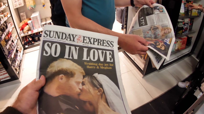 meghan markle : LONDON, UK - MAY 20, 2018: Crowd reading The Sunday Express front cover newspaper British press kiosk featuring portraits of Prince Harry and Meghan Markle Royal Wedding So In Love