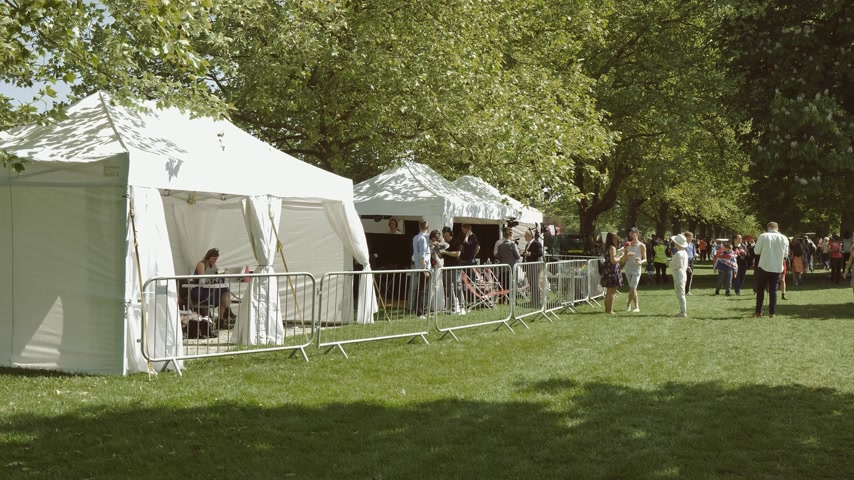 meghan markle : WINDSOR, UNITED KINGDOM - MAY 19, 2018: Wide view of White tents of Media TV stations tents in green park reporting live to cover the royal wedding marriage celebration of Prince Harry, Duke and Meghan Markle - Stock Footage