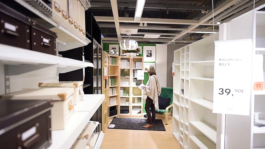 книжный магазин : PARIS, FRANCE - CIRCA 2018: Modern IKEA furniture store with woman customer buying library furniture and decoration warehouse goods - time lapse fast motion