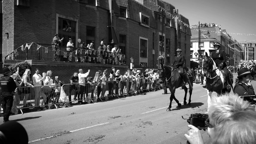 windsor : WINDSOR, UNITED KINGDOM - MAY 19, 2018: Saluting the Royal Guards on horses march in street around Windsor Castle after procession celebrate wedding of Prince Harry of Wales and Ms Meghan Markle - black and white Stock Footage