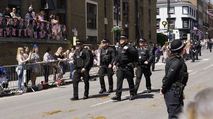 meghan markle : WINDSOR, UNITED KINGDOM - MAY 19, 2018: Crowd applauding MET police march in street around Windsor Castle after procession celebrate wedding of Prince Harry of Wales and Ms Meghan Markle