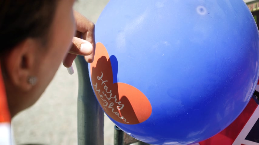 balão : WINDSOR, BERKSHIRE, UNITED KINGDOM - MAY 19, 2018: Woman with blue balloon waiting for the royal couple during royal wedding marriage celebration of Prince Harry, and Meghan Markle Stock Footage