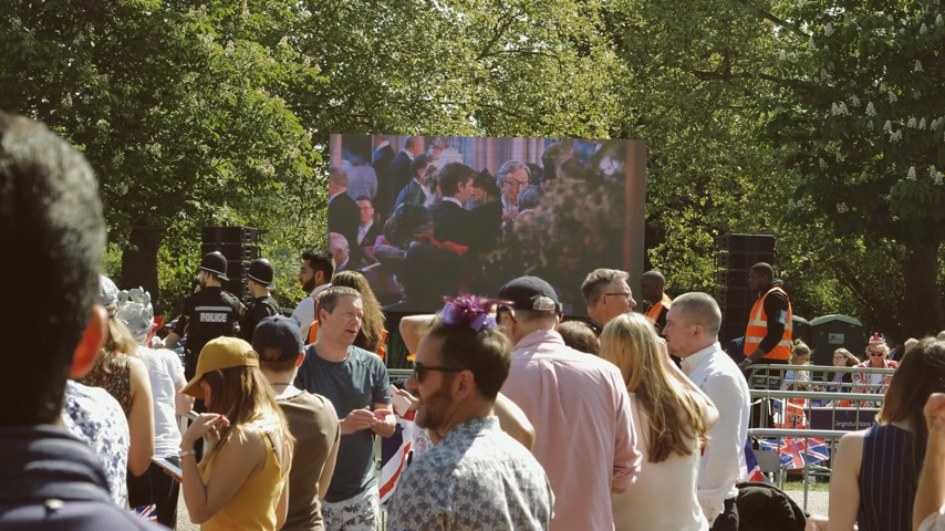 meghan markle : WINDSOR, UNITED KINGDOM - MAY 19, 2018: People watching the Royal Wedding on a big large screen in Long Road park in Windsor during Prince Harry and Meghan Markle wedding - live broadcast Stock Footage