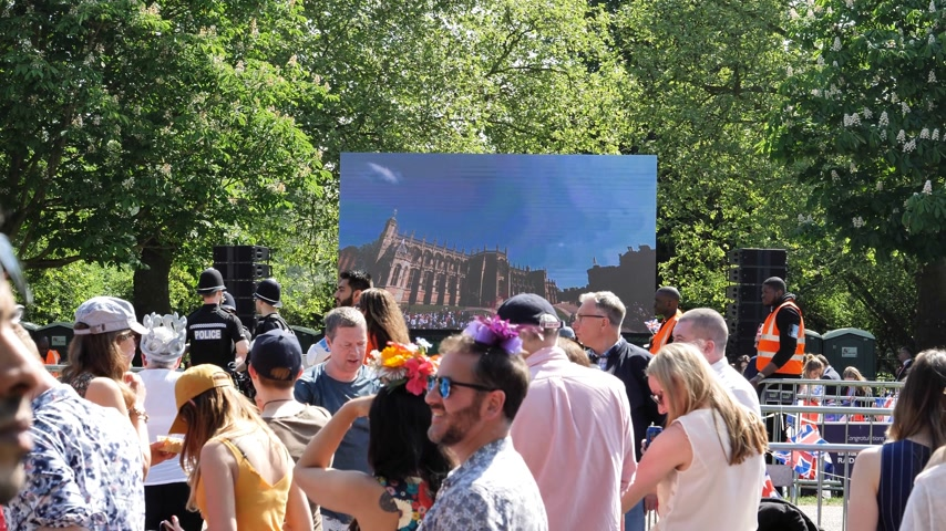 celebridade : WINDSOR, UNITED KINGDOM - MAY 19, 2018: People watching the Windsor Castle and Royal Wedding on a big large screen in Long Road park in Windsor during Prince Harry and Meghan Markle wedding - live broadcast