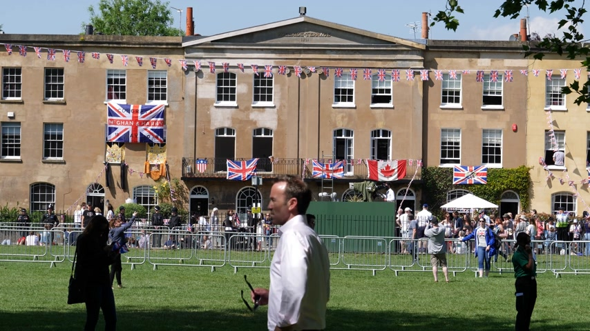windsor : WINDSOR, BERKSHIRE, UNITED KINGDOM - MAY 19, 2018: Adelaide Terrace building with UK US and Canada flags on facade and crowd celebration during the royal couple marriage celebration of Prince Harry and Meghan Markle Stock Footage