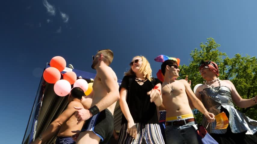 minority group : STRASBOURG, FRANCE - JUN 10, 2017: Group excited gay men women people supporters dancing with rainbow flag behind in slow motion against clear peaceful blue sky LGBT visibility march pride