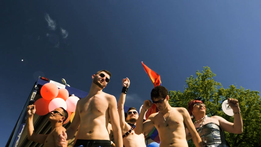 lesbijki : STRASBOURG, FRANCE - JUN 10, 2017: Group excited gay woman and men dancing with rainbow flag behind in slow motion at Lesbian Gay Bisexual Transgender LGBT visibility march pride - descending truck Wideo